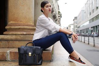 Cómo combinar: blusa de manga larga a lunares blanca, vaqueros pitillo azul marino, zapatillas slip-on de ante negras, bolso de hombre de cuero negro