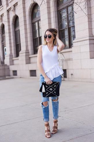 Cómo combinar: blusa sin mangas con volante blanca, vaqueros pitillo desgastados azules, sandalias de tacón de cuero marrónes, cartera sobre de punto negra