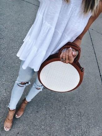 Cómo combinar una blusa sin mangas blanca: Para un atuendo tan cómodo como tu sillón opta por una blusa sin mangas blanca y unos vaqueros pitillo desgastados celestes. Con el calzado, sé más clásico y elige un par de sandalias con cuña de cuero marrón claro.