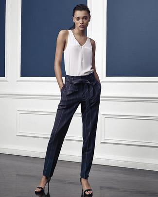 Cómo combinar: blusa sin mangas de seda blanca, pantalón de pinzas de rayas verticales azul marino, sandalias de tacón de cuero negras