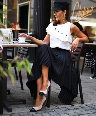 Cómo combinar: blusa sin mangas con volante blanca, falda larga plisada negra, zapatos de tacón de cuero en blanco y negro, gorra inglesa negra