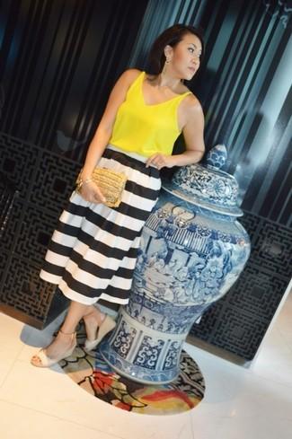 Cómo combinar: blusa sin mangas amarilla, falda midi de rayas horizontales en blanco y negro, sandalias con cuña de cuero en beige, cartera sobre de paja marrón claro