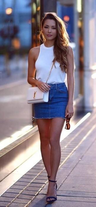 Cómo combinar: blusa sin mangas blanca, minifalda vaquera azul, sandalias de tacón de ante azul marino, bolso bandolera de cuero blanco