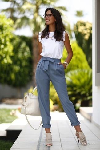 Cómo combinar: blusa sin mangas con volante blanca, pantalón de pinzas azul, sandalias de tacón de ante сon flecos en beige, bolso de hombre de cuero blanco
