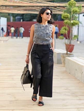 Cómo combinar: blusa sin mangas bordada gris, pantalones anchos negros, sandalias planas de cuero negras, bolso de hombre de cuero negro