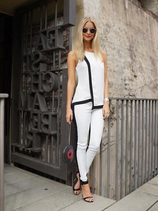 Cómo combinar: blusa sin mangas en blanco y negro, pantalones pitillo en blanco y negro, sandalias de tacón de cuero negras, cartera sobre de cuero estampada negra