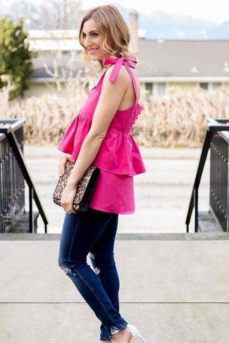 Cómo combinar: blusa sin mangas con volante rosa, vaqueros pitillo desgastados azul marino, sandalias de tacón de cuero blancas, cartera sobre de cuero de leopardo marrón