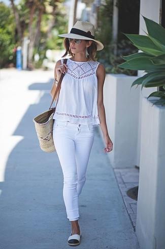 Cómo combinar: blusa sin mangas de crochet blanca, vaqueros pitillo blancos, alpargatas en blanco y negro, bolsa tote de paja en beige