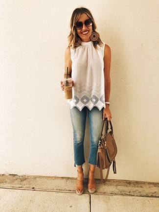 Cómo combinar: blusa sin mangas con ojete blanca, vaqueros pitillo azules, sandalias con cuña de cuero marrónes, bolso de hombre de cuero marrón