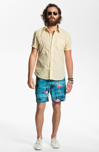 Cómo combinar: camisa de manga corta amarilla, pantalones cortos estampados en turquesa, tenis en beige