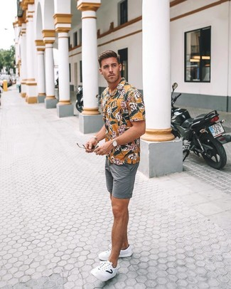 Cómo combinar: camisa de manga corta con print de flores amarilla, pantalones cortos grises, tenis de cuero blancos, reloj de cuero marrón claro