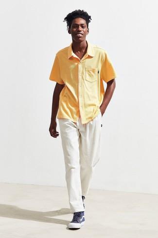 Cómo combinar: camisa de manga corta amarilla, vaqueros de pana blancos, zapatillas altas azul marino