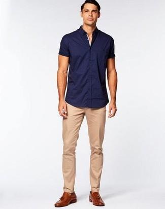 Cómo combinar: camisa de manga corta azul marino, pantalón chino marrón claro, mocasín con borlas de cuero marrón