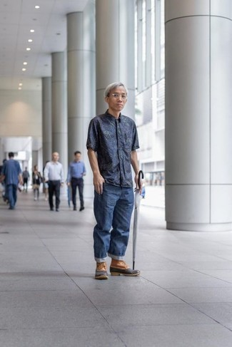 Moda para hombres de 40 años: Empareja una camisa de manga corta estampada azul marino con unos vaqueros azules para un look diario sin parecer demasiado arreglada. ¿Quieres elegir un zapato informal? Elige un par de botas para la nieve marrón claro para el día.