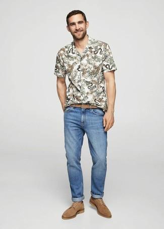 Cómo combinar: camisa de manga corta con print de flores blanca, vaqueros azules, zapatos derby de ante marrón claro, correa de cuero tejida marrón claro