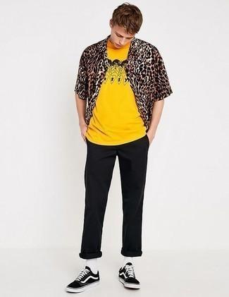 Cómo combinar un pantalón chino negro para hombres adolescentes: Opta por una camisa de manga corta de leopardo marrón y un pantalón chino negro para lidiar sin esfuerzo con lo que sea que te traiga el día. Tenis de lona en negro y blanco son una opción muy buena para complementar tu atuendo.