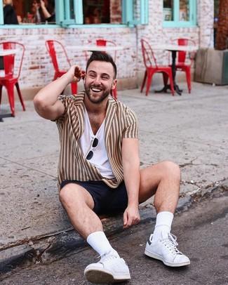 Cómo combinar: camisa de manga corta de rayas verticales marrón claro, camiseta con cuello en v blanca, pantalones cortos negros, tenis de cuero blancos