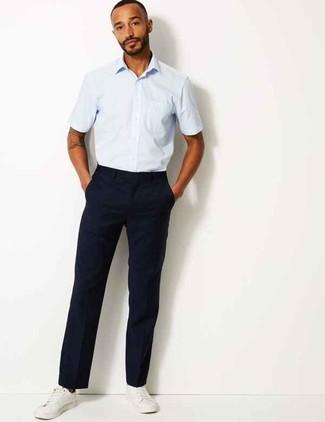Cómo combinar: camisa de manga corta celeste, pantalón chino azul marino, tenis de cuero blancos