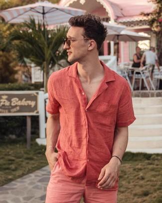 Cómo combinar: camisa de manga corta de lino roja, pantalones cortos rosa, gafas de sol marrónes