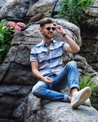 Cómo combinar: camisa de manga corta de rayas horizontales celeste, vaqueros azules, tenis blancos