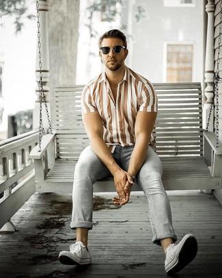 Cómo combinar: camisa de manga corta de lino de rayas verticales marrón, vaqueros grises, tenis de lona blancos, gafas de sol negras