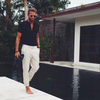 Cómo combinar: camisa de manga corta negra, pantalón chino en beige, sandalias de cuero negras