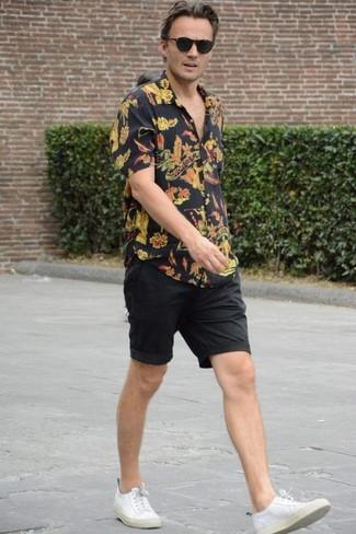 Cómo combinar: camisa de manga corta con print de flores negra, pantalones cortos negros, tenis de lona blancos, gafas de sol negras