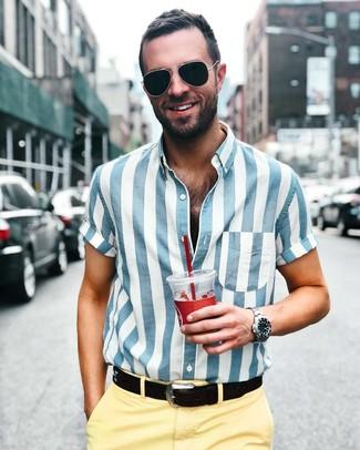 Cómo combinar: camisa de manga corta de rayas verticales en blanco y azul, pantalón chino amarillo, correa de cuero negra, gafas de sol negras