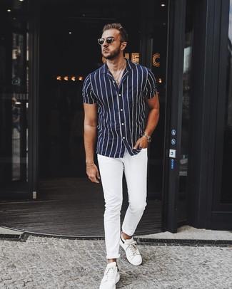 Cómo combinar: camisa de manga corta de rayas verticales en azul marino y blanco, pantalón chino blanco, tenis de cuero blancos, gafas de sol negras