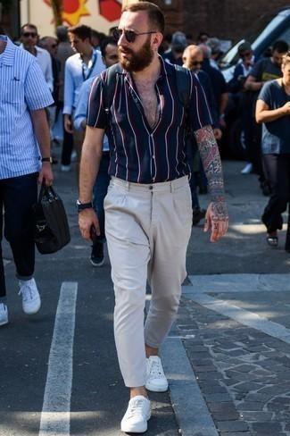 Outfits hombres: Para un atuendo que esté lleno de caracter y personalidad intenta ponerse una camisa de manga corta de rayas verticales azul marino y un pantalón chino gris. Tenis de cuero blancos son una opción atractiva para complementar tu atuendo.