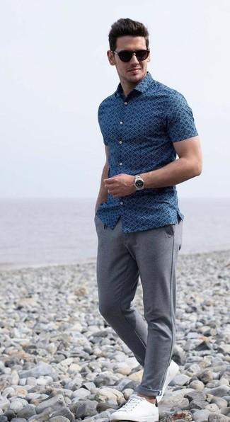Cómo combinar: camisa de manga corta estampada azul, pantalón de chándal gris, tenis de cuero blancos, gafas de sol en marrón oscuro