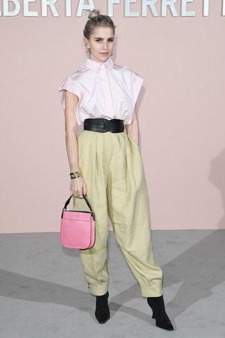 Cómo combinar: camisa de manga corta rosada, pantalones anchos amarillos, botines de elástico negros, cartera de cuero rosa