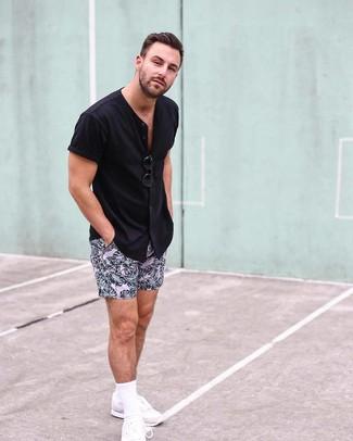 Cómo combinar: camisa de manga corta negra, pantalones cortos estampados rosados, deportivas blancas, gafas de sol negras