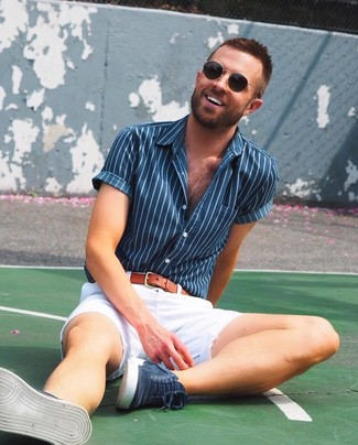 Cómo combinar: camisa de manga corta de rayas verticales azul marino, pantalones cortos blancos, zapatillas altas de ante azul marino, correa de cuero en tabaco