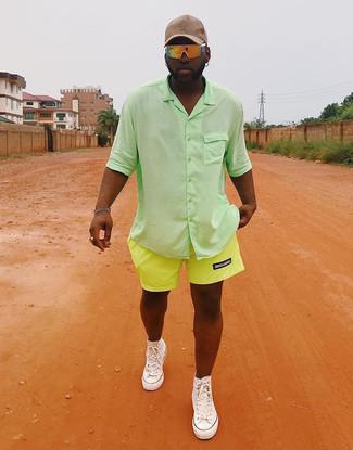 Cómo combinar: camisa de manga corta verde, pantalones cortos en amarillo verdoso, zapatillas altas de lona blancas, gorra de béisbol en beige