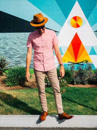 Cómo combinar: camisa de manga corta rosada, pantalón chino marrón claro, zapatos derby de cuero en tabaco, sombrero de paja en tabaco