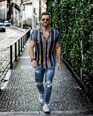 Cómo combinar: camisa de manga corta de rayas verticales azul marino, vaqueros pitillo desgastados azules, tenis blancos, gafas de sol negras