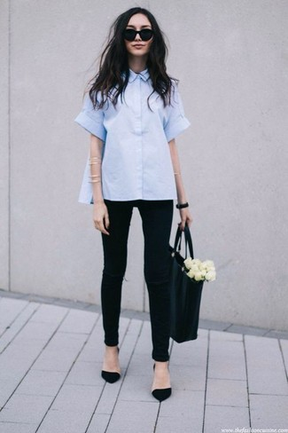 Cómo combinar: camisa de manga corta celeste, vaqueros pitillo desgastados negros, zapatos de tacón de ante negros, bolsa tote de cuero negra