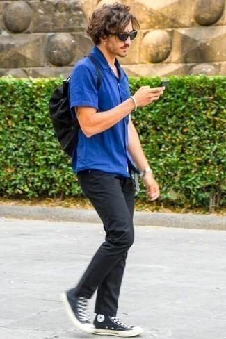 Cómo combinar unas zapatillas altas de lona en negro y blanco: Empareja una camisa de manga corta azul con unos vaqueros negros para un almuerzo en domingo con amigos. Si no quieres vestir totalmente formal, complementa tu atuendo con zapatillas altas de lona en negro y blanco.