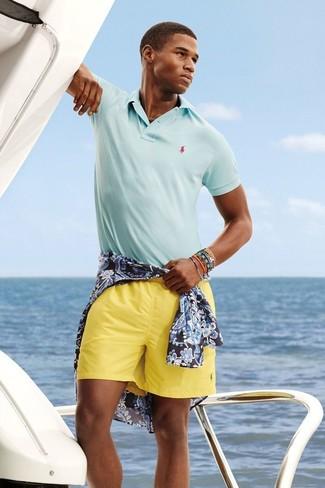 Cómo combinar: camisa de manga larga con print de flores azul marino, camisa polo celeste, pantalones cortos amarillos, pulsera en multicolor