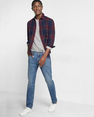 Cómo combinar: camisa de manga larga de tartán azul marino, camiseta de manga larga gris, vaqueros azules, tenis de cuero blancos