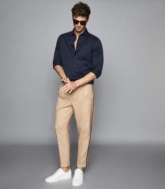 Cómo combinar una camisa de manga larga azul: Para un atuendo que esté lleno de caracter y personalidad empareja una camisa de manga larga azul junto a un pantalón chino marrón claro. Si no quieres vestir totalmente formal, elige un par de tenis de cuero blancos.