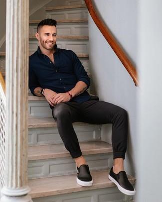 Cómo combinar: camisa de manga larga azul marino, pantalón chino negro, zapatillas slip-on de cuero negras, reloj de cuero negro