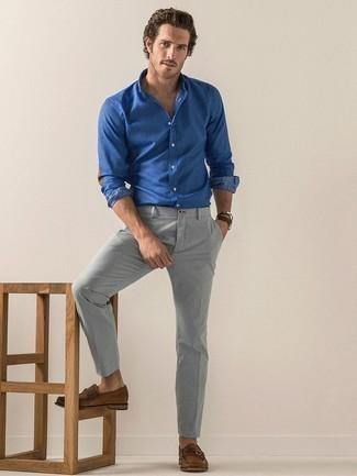 Cómo combinar un pantalón chino gris: Opta por una camisa de manga larga de cambray azul y un pantalón chino gris para conseguir una apariencia relajada pero elegante. ¿Te sientes ingenioso? Dale el toque final a tu atuendo con mocasín de ante marrón.