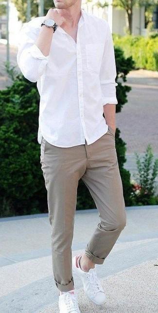 Outfits hombres en clima cálido: Empareja una camisa de manga larga blanca con un pantalón chino marrón claro para cualquier sorpresa que haya en el día. ¿Quieres elegir un zapato informal? Opta por un par de tenis de cuero blancos para el día.