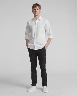 Cómo combinar un pantalón chino negro: Considera emparejar una camisa de manga larga blanca con un pantalón chino negro para una vestimenta cómoda que queda muy bien junta. Si no quieres vestir totalmente formal, elige un par de tenis de cuero blancos.