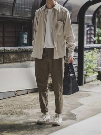 Outfits hombres: Considera emparejar una camisa de manga larga en beige con un pantalón chino verde oliva para un almuerzo en domingo con amigos. ¿Quieres elegir un zapato informal? Elige un par de zapatillas altas de lona blancas para el día.