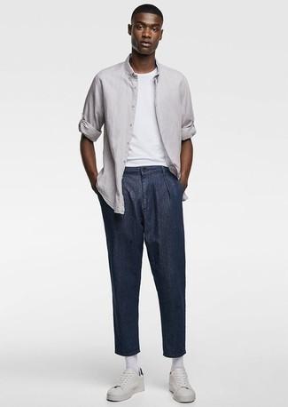 Cómo combinar unos tenis: Elige una camisa de manga larga gris y un pantalón chino azul marino para conseguir una apariencia relajada pero elegante. ¿Te sientes valiente? Completa tu atuendo con tenis.
