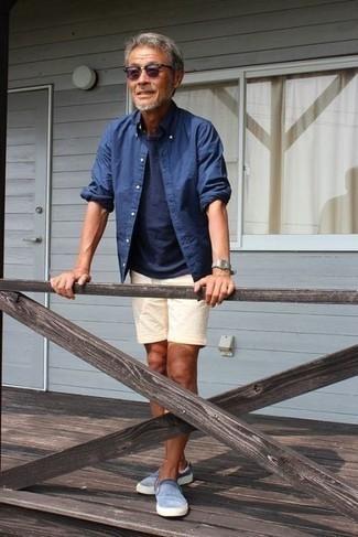 Outfits hombres: Los días ocupados exigen un atuendo simple aunque elegante, como una camisa de manga larga de cambray azul y unos pantalones cortos de lino en beige. Zapatillas slip-on celestes son una opción práctica para completar este atuendo.