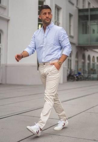 Outfits hombres en clima cálido: Los días ocupados exigen un atuendo simple aunque elegante, como una camisa de manga larga celeste y un pantalón chino en beige. ¿Quieres elegir un zapato informal? Complementa tu atuendo con tenis de lona en blanco y rojo para el día.